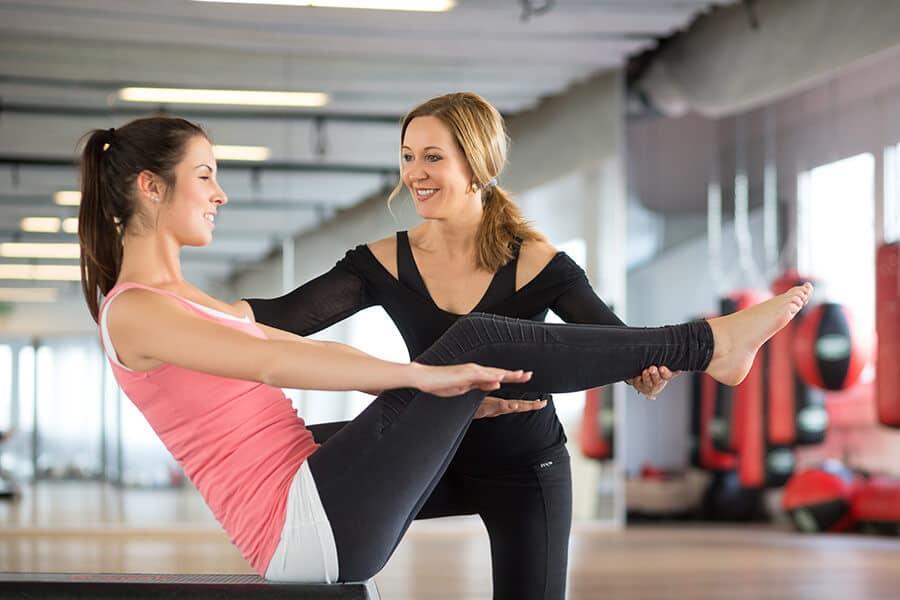 Trainerin betreut eine Frau beim Training
