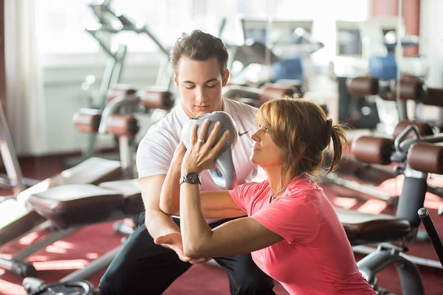 Frau mit Kettlebell beim Muskeltraining mit Trainer in Darmstadt